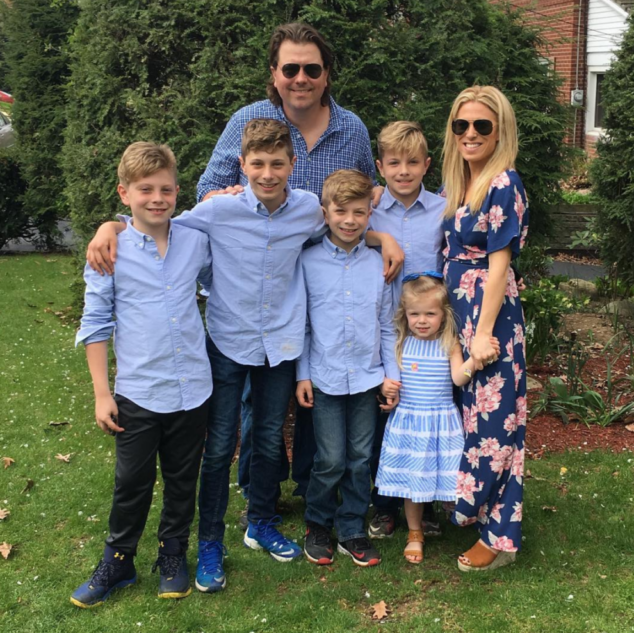 Outdoor family photo of two parents and five children.