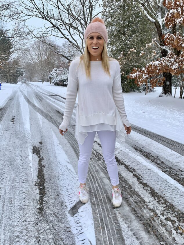 woman wearing white standing in the snow in the winter